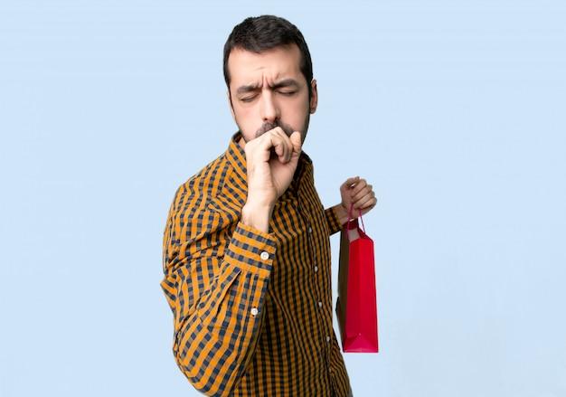Homem com sacos de compras está sofrendo com tosse e se sentindo mal no fundo azul isolado