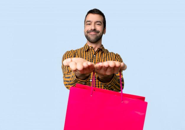 Homem com sacos de compras segurando copyspace imaginário na palma da mão para inserir um anúncio no fundo azul isolado