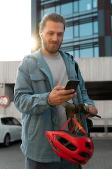 Homem com scooter olhando para o telefone