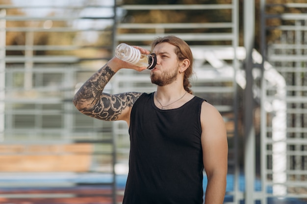 Homem com sede beber esportes cocktail de garrafa durante o treinamento de musculação