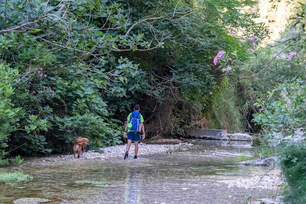 Homem com seu cachorro andando ao longo do rio