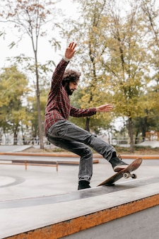 Homem com skate ao ar livre no parque da cidade