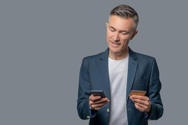 Homem com smartphone e cartão de crédito