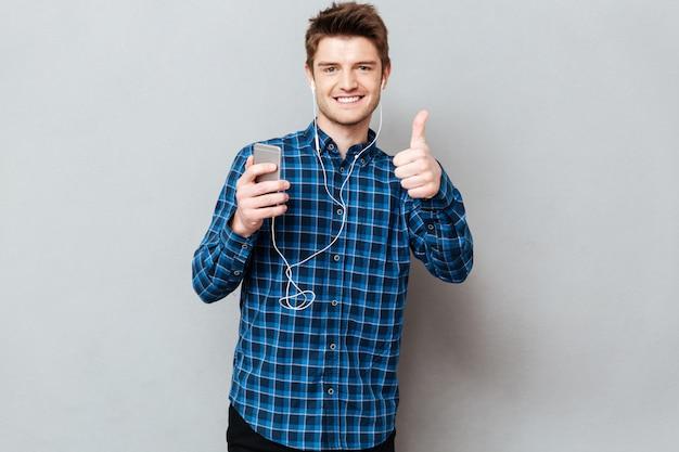 Homem com smartphone e fones de ouvido, mostrando os polegares
