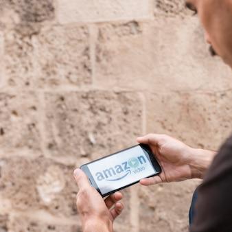 Homem, com, smartphone, mostrando, amazon, principal, vídeo, app