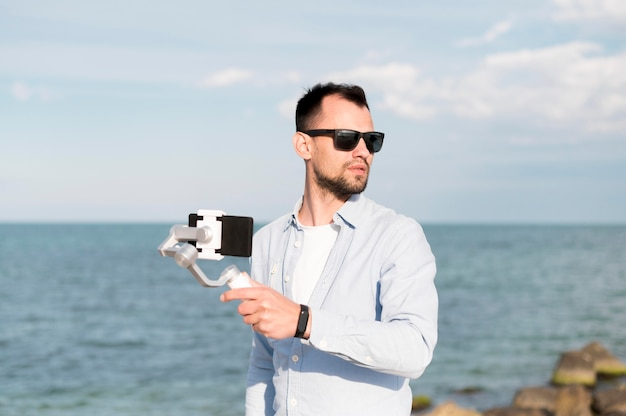 Homem com smartphone na beira-mar