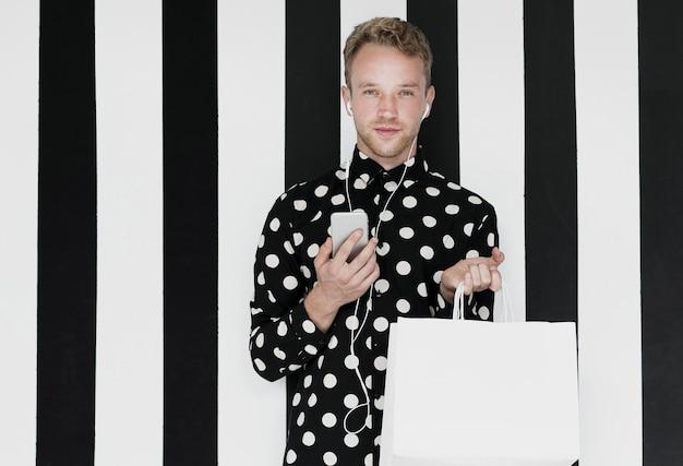 Homem com smartphone, olhando para a câmera