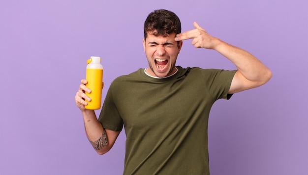 Homem com smoothy parecendo infeliz e estressado, gesto suicida fazendo sinal de arma com a mão, apontando para a cabeça