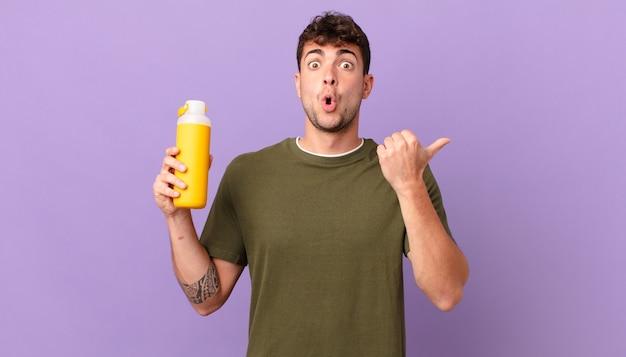 Homem com smoothy parecendo surpreso em descrença, apontando para o objeto ao lado e dizendo uau, inacreditável