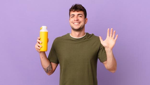 Homem com smoothy sorrindo feliz e alegre, acenando com a mão, dando as boas-vindas e cumprimentando você ou dizendo adeus