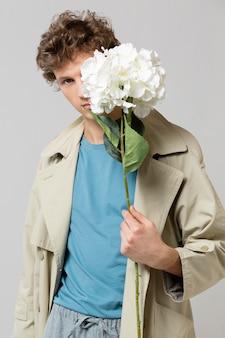 Homem com sobretudo segurando flores