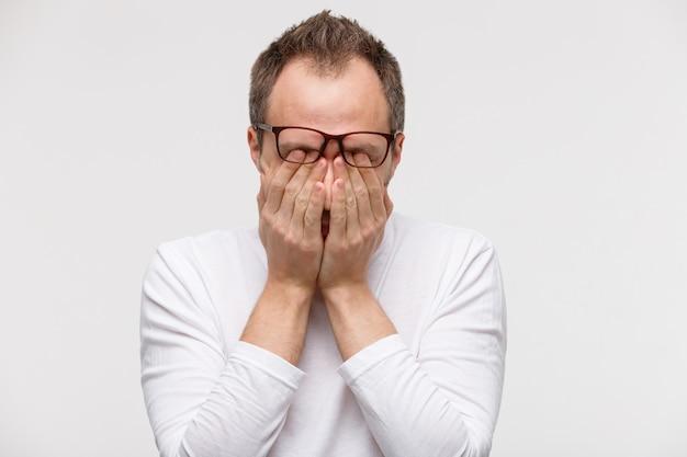 Homem com sono de óculos, esfregando os olhos, sente-se cansado depois de trabalhar no laptop