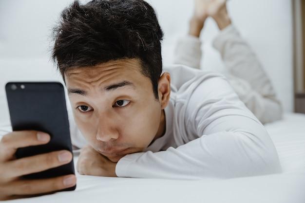 Homem com sono usando smartphone na cama
