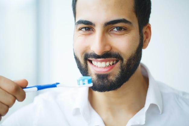 Homem com sorriso lindo, saudáveis dentes brancos com escova de dentes.