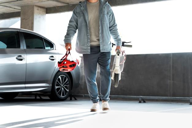 Homem com sua scooter em um estacionamento coberto