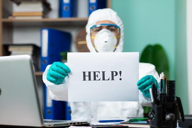 Homem com suíte branca especial segurando uma palavra de ajuda no escritório