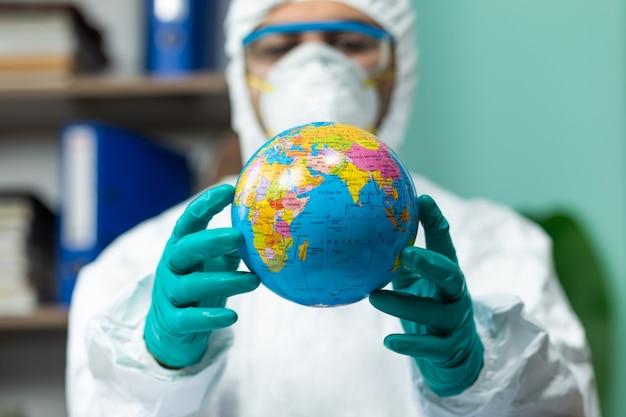Homem com suíte especial branca segurando o globo terrestre com a mão no escritório