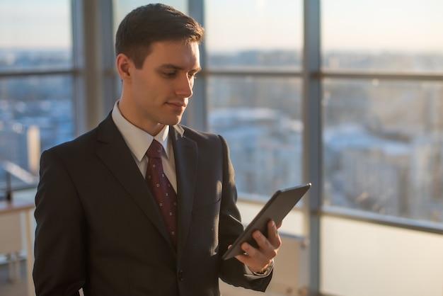 Homem com tablet digital em pé no interior do escritório moderno.
