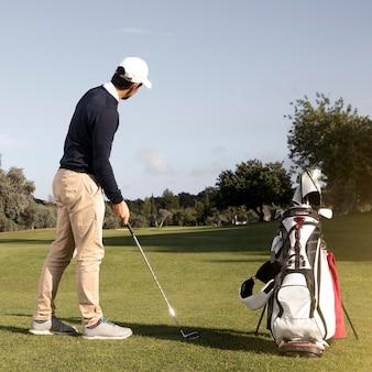 Homem com taco de golfe no campo jogando