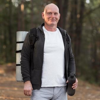 Homem com tapete de ioga na frente