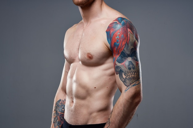 Homem com tatuagem de imprensa bombeada no estúdio de visualização recortada nos braços