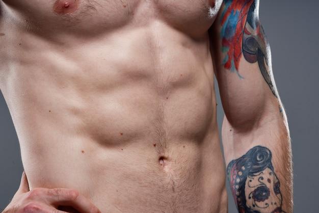 Homem com tatuagem de torso inflado nos braços