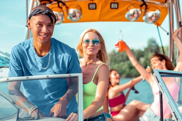 Homem com tatuagem. jovem sorridente com tatuagens nas duas mãos e sua namorada dirigindo um iate pelo rio com os amigos dançando a bordo