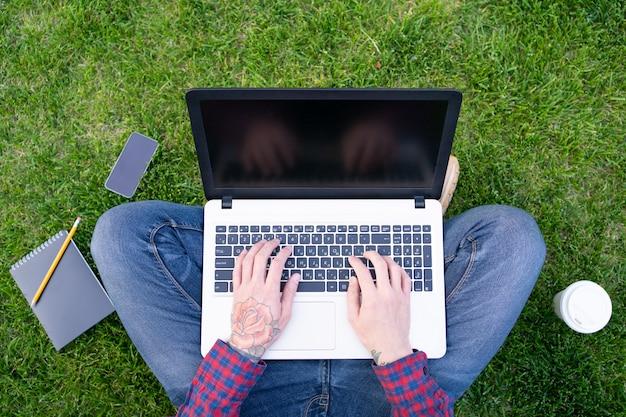 Homem com tatuagem rosa na mão digitando no laptop