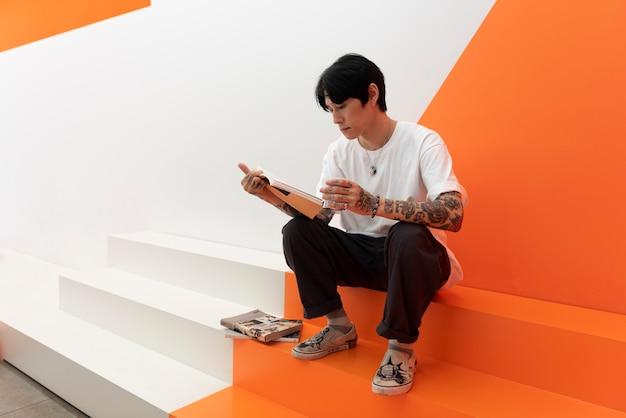 Homem com tatuagens, bebendo café e lendo um livro em um café