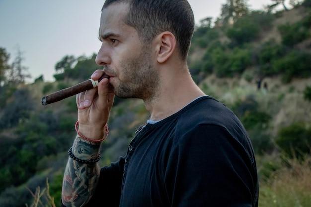Homem com tatuagens e cigarro fuma ao ar livre