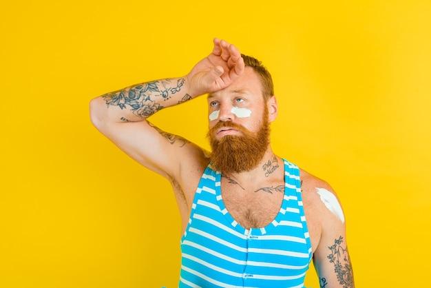 Homem com tatuagens e maiô passa protetor solar