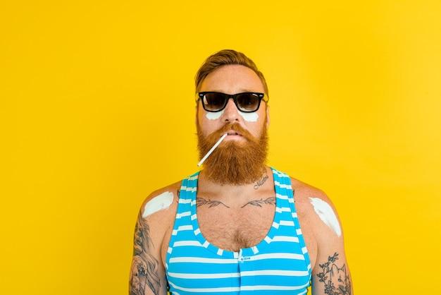 Homem com tatuagens e maiô passa protetor solar Foto Premium