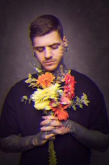 Homem com tatuagens, segurando um buquê de flores