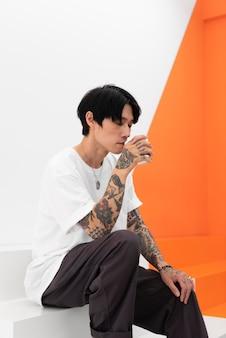 Homem com tatuagens tomando café em um café