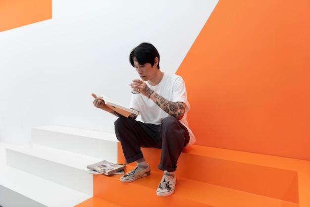 Homem com tatuagens, tomando uma xícara de café em um café e lendo livros