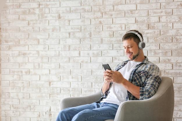 Homem com telefone celular e fones de ouvido relaxando em casa