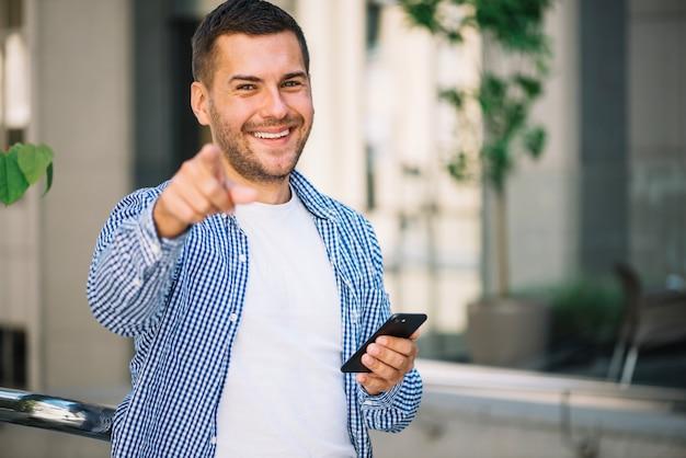 Homem com telefone inteligente apontando para você