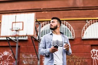 Homem, com, telefone móvel, ficar, em, quadra basquetebol