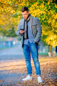 Homem com telefone móvel no beco de temporada outono.