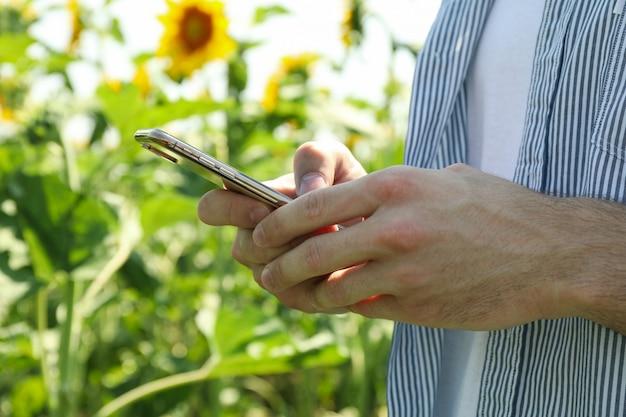 Homem com telefone no campo de girassol.