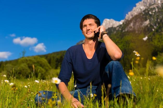 Homem com telefone sentado nas montanhas