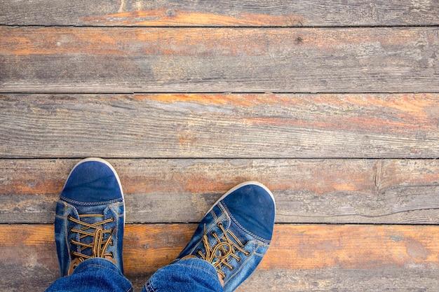 Homem com tênis da moda fica em um velho piso de madeira. copiar spase para texto