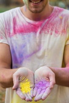 Homem com tinta em pó nas mãos no holi