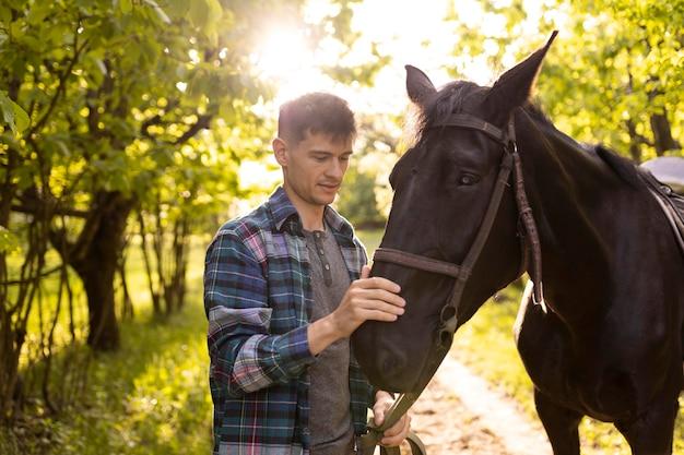 Homem com tiro médio acariciando o cavalo ao ar livre