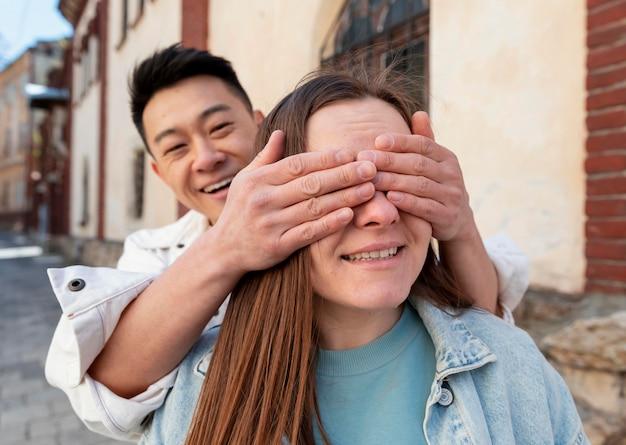 Homem com tiro médio cobrindo os olhos da mulher