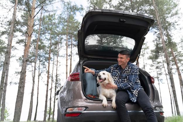 Homem com tiro médio segurando cachorro no porta-malas
