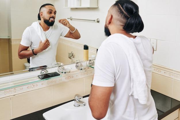 Homem com toalha no ombro, escovando os dentes em frente ao espelho do banheiro pela manhã