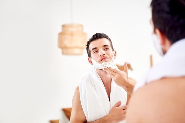 Homem com toalha nos ombros espalha o rosto com espuma de barbear enquanto fica em pé na banheira perto do espelho