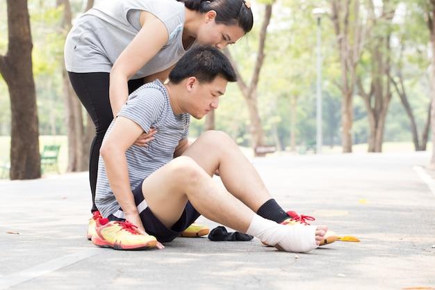Homem com tornozelo torcido, recebendo ajuda de mulher
