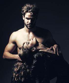 Homem com torso musculoso segurando mulher no cabelo comprido